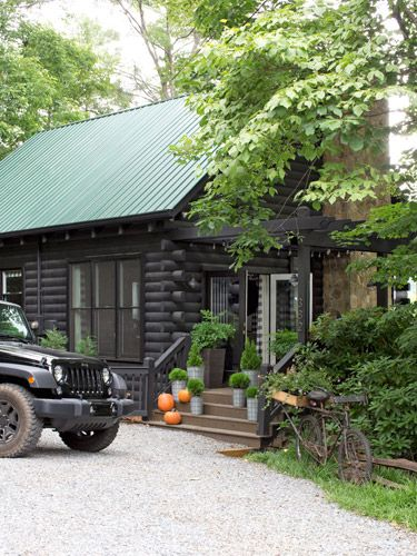 A couple of coats of a darker forest green paint on the metal roof and black on the logs took the house from outdated to modern-day rustic.