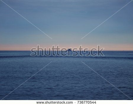 ferry in the open sea on the horizon under the evening sky