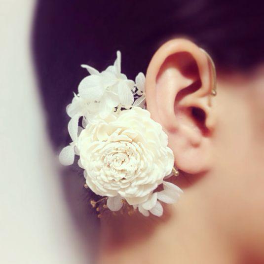 おおきな白花がメインの白いイヤーカフです。真っ白なプリザーブドフラワーを集めて、大きなお花をメインに添えました。ガーリーなお洋服にはもちろん、シンプルなコーディネートに女性らしいアクセントとしてもお使い頂けます。お着物にもドレスにも、夏には浴衣につけてもいいと思います♪ また、特別な日のパーティーでも耳元を華やかに飾ってくれますよ♪誕生日やクリスマス、記念日や感謝の気持ちを込めたプレゼントに...