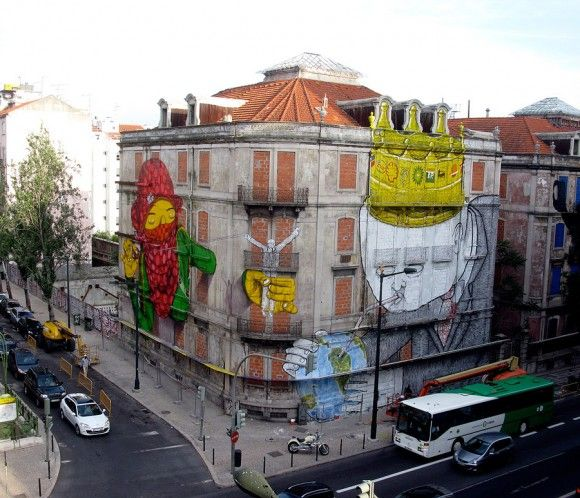 It's an amazing huge mural artwork, created in Lisbon, by street artists: Os Gémeos & Blu!