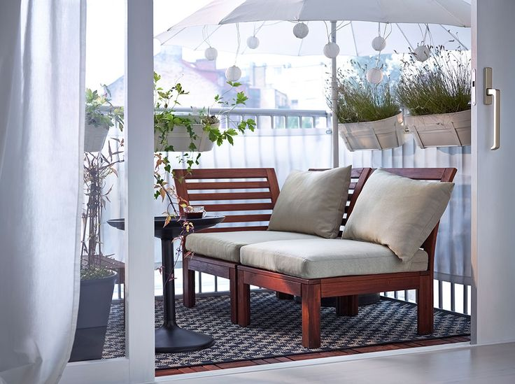 A balcony with brown wooden modular seating with beige seat/back cushions and a black round tray table ((IKEA))