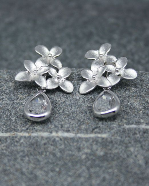 Floral earrings with crystal drop.  These very eye catching triple flower earrings are perfect for any occasion, weddings, anniversaries and birthdays.  The flowers measure 15 x 14mm approx with a sterling silver post to backs. The crystal drops each measure 11 x 7mm.  The overall length of the earrings is 23mm.  Flowers are rhodium plated over brass. Sterling silver posts on flowers. Crystals are set in rhodium plated over brass settings.  All of our jewellery comes in blue or silver box...