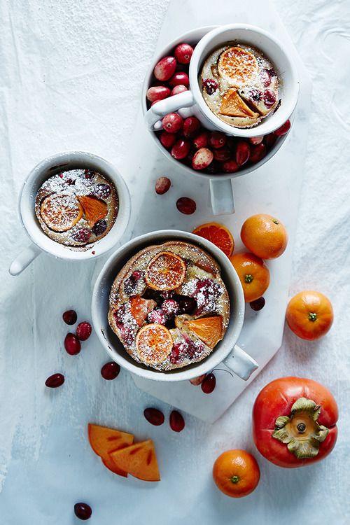 Allspice Persimmon and Cranberry Clafoutis: sugar, water, allspice berries, cranberries, persimmon, clementine, brandy, eggs, flour, half and half, vanilla, ground allspice