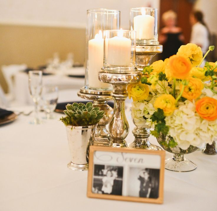 table centerpiece is made up of yellow ranunculus and white hydrangea placed in a footed mercury glass vessel and is paired with a trio of mercury glass pedestal candle holders and a succulent placed in a silver mint julep cup. the bride and groom chose  a photograph to correspond with their age of each table number