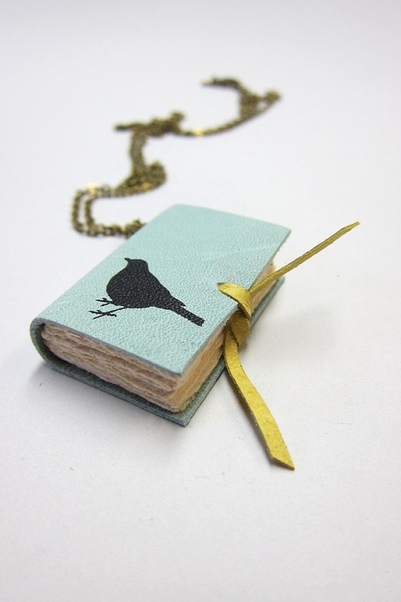 This is a one of a kind charming little hand-bound light blue leather book necklace. The 112 pages (counting both sides) are hand torn and sewed. It opens up nicely. It is lined with a decorative end sheet and held closed by its playful leather ties.