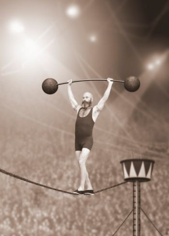 Trapeze artist walking on tightrope while weight lifting