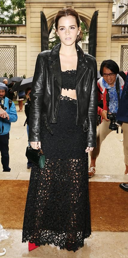 JULY 10, 2014  Emma Watson toughened up her sexy lacy black Valentino separates at the Valentino Couture fall/winter 2014 show with a black moto jacket and a solo Delfina Delettrez pearl-ended earring. A miniature M2Malletier top-handle clutch, Anita Ko rings, and red pumps completed her look