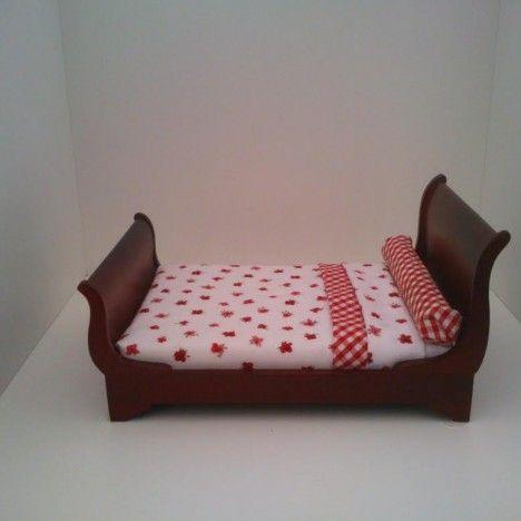 Cama de trineo en madera color caoba vestida con conjunto de cama en rojo y blanco.