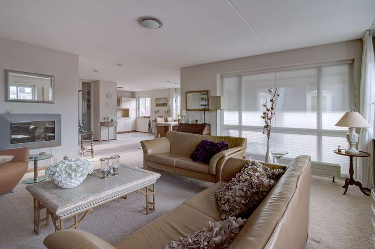 De woonkamer met een afmeting van circa 50m² is bijzonder royaal. Vijf gevelramen en twee grote puien waarvan één met dubbele deuren zorgen voor veel licht. De ligging is op het zuidoosten en het zuidwesten  www.theo-keijzers.nl