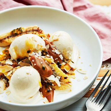 Bananen älskar att bli grillad och serverad med vaniljglass. Gott så, men ännu bättre blir den här grillade desserten tillsammans med syrlig passionsfrukt, rostad kokos och len kolasås. Självklart går det lika bra att steka bananen i en stekpanna med lite smör.