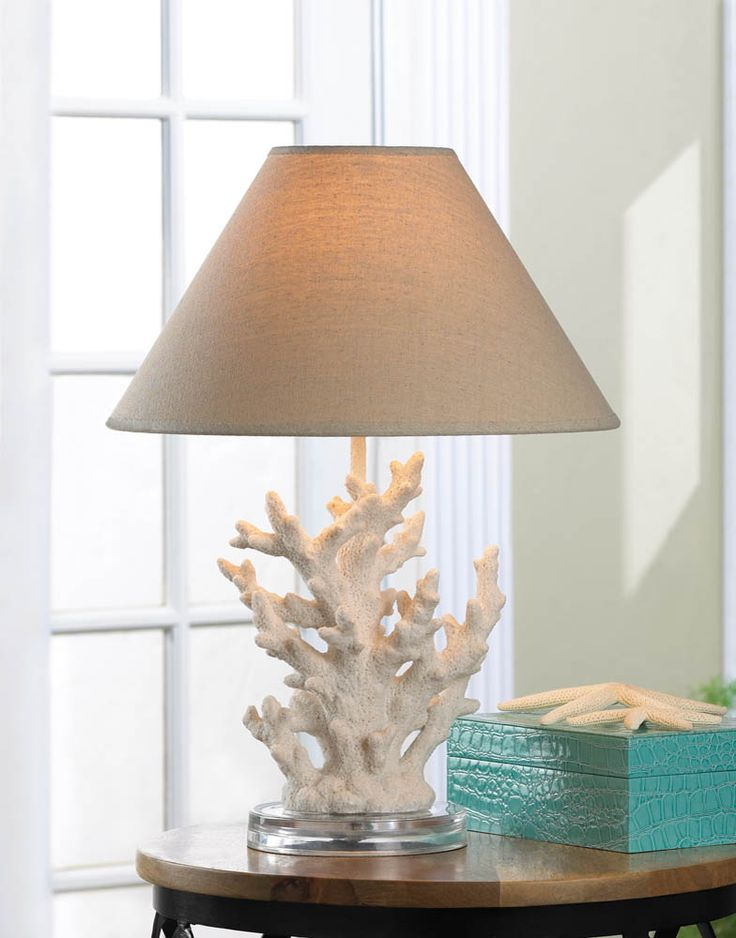 White Coral Table Lamp --- A splash of seaworthy style to light up your life! This stunning table lamp features artistically rendered ivory sprigs of coral topped with a handsome neutral-color shade. Turn on the lamp and the coral and your room with light up with a warm and inviting glow.