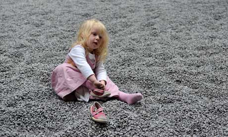 Day at the beach? A young girl sits down on Ai Weiwei's porcelain sunflower seeds in Tate Modern's Turbine Hall. Photograph: Andy Rain/EPA