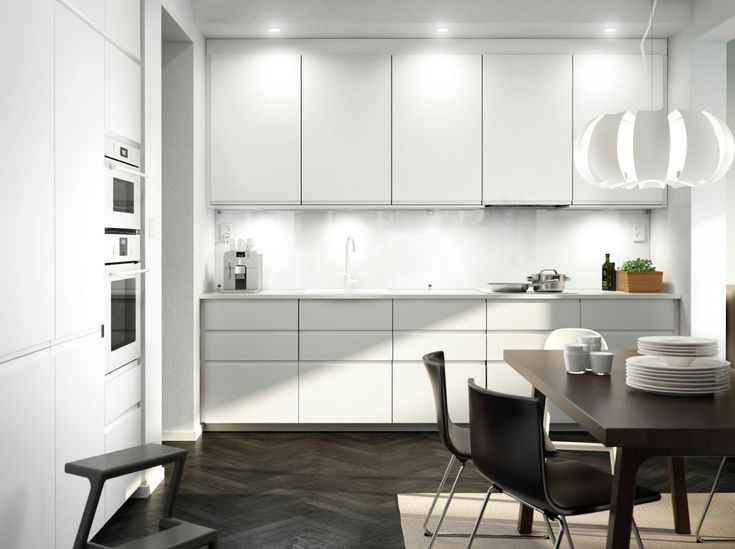 A white kitchen with white appliances and black-brown leather chairs and dining table.