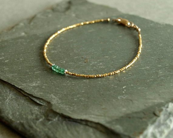 This gold emerald bracelet has stunning and beautiful small untreated natural Zambian emeralds at its center, surrounded by tiny 14K gold vermeil beads. This small gemstone bracelet closes with a 14K goldfilled lobster clasp.  The emeralds in this dainty feminine bracelet are real beauties -- a gorgeous translucent emerald green. This bracelet is delicate and elegant, petite enough for layering, but striking enough on its own, day or evening.  Bracelet currently available in 7 1/4 inch s...