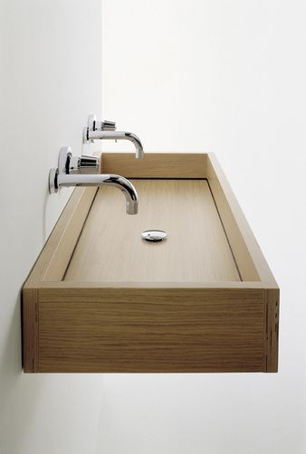 The Woodline washbasin recalls both the simplicity and rituality of oriental bathrooms: a large and shallow rectangular basin in plywood, wi...