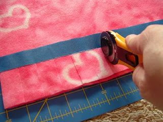 Putting Painters Tape down to mark where to stop cutting with your rotary! Smart! This site teaches other methods to the no sew fleece blankets.