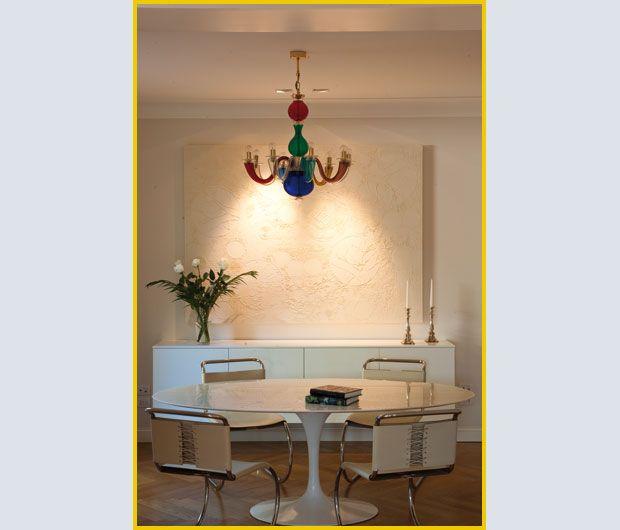 Nella zona pranzo, TAVOLO Tulip di Eero Saarinen abbinato alle SEDIE in pelle della Mr Collection di Mies van der Rohe, tutti prodotti da Knoll, e alla SOSPENSIONE in cristallo multicolore di Gio Pont