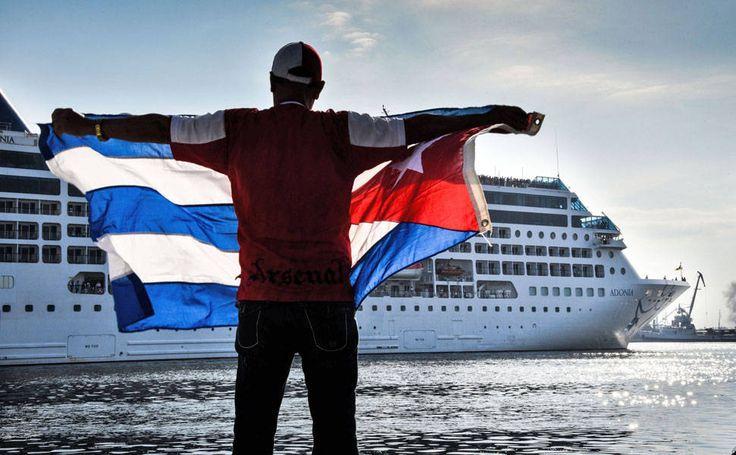 Um homem acena com uma bandeira cubana na margem do rio Malecon, como o primeiro navio de cruzeiro vindo dos EUA para Cuba em 50 anos, no porto de Havana