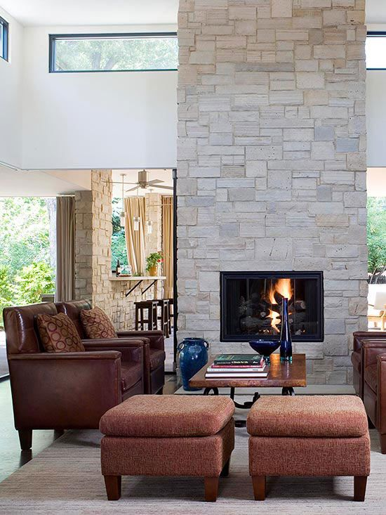 Two walls of retractable glass doors seamlessly connect this interior sitting area to the exterior patio and bar. A large stone fireplace in the center of both rooms lends warmth and subtle separation and helps the spaces feel more grounded./