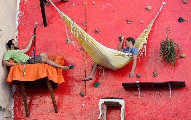 """La casa verticale - L'artista brasiliano Tiago Primo e suo fratello Gabriel in bilico su un muro a Rio De Janeiro. La bizzarra casa """"verticale"""" è stata costruita su una parete da arrampicata (Reuters)"""