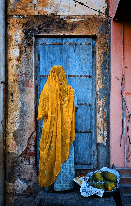 A woman in India, dressed in traditional, colorful garb, returns home from a street market.