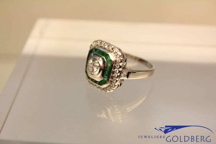 """Very beautiful and unique white gold ring with in the middle a 0.65ct brilliant cut diamond (P1, TW), surrounded by 18 small emeralds in turn surrounded by 28 0.015ct brilliant cut diamonds. A very special and """"living"""" piece of art. For more information visit our site: http://www.goldbergjuweliers.nl/en/white-gold-square-ring-with-emeralds-and-diamands.html"""