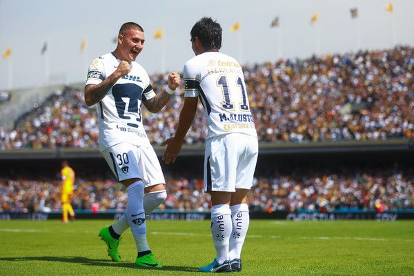 (R-L) Matias Alustiza of Pumas celebrates with teammate Nicolas Castillo after scoring the second goal of his team during the 5th round match between Pumas UNAM and Tigres UANL as part of the Torneo Clausura 2018 Liga MX at Olimpico Universitario Stadium on February 4, 2018 in Mexico City, Mexico.