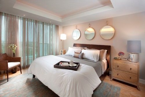 Runde Spiegel auf dem Overhead Display, weiche karierte Vorhänge dienen ein schickes Chrom Lampe und Blumen Vasen als feminine Akzente für das Master-Schlafzimmer. Foto: