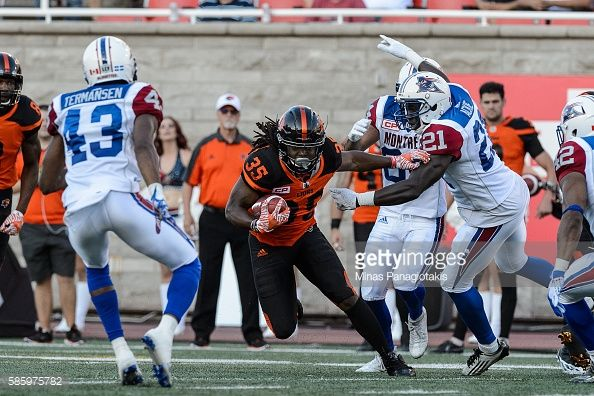 Running back Shaquille MurrayLawrence of the BC Lions protects the ball against linebacker Chris Ackie of the Montreal Alouettes during the CFL game...