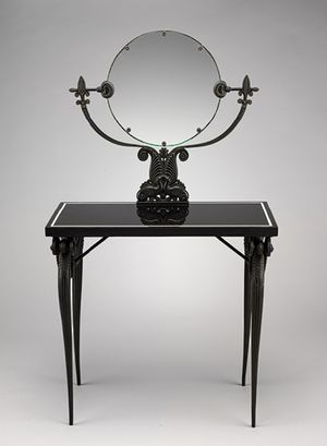 Here is an image of a dressing table constructed in 1925 by Armand-Albert Rateau. The materials that were used to construct this dressing table are bronze, basalt, and mirror glass. This table takes many different elements like the actual mirror reflecting past styles used in Pompeiian models of work.