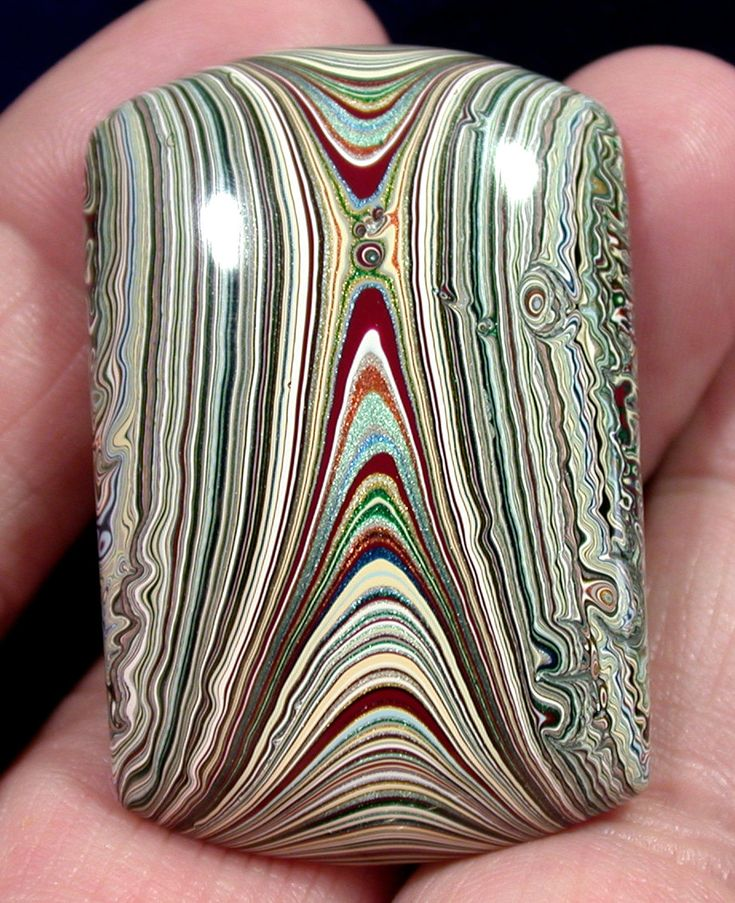 Fordite or Detroit Agate - if this means what I think it means, it is the packed layers of paint off the wall of a car-painting facility. Siince the paint is enamel and baked on, it cuts and polishes up nicely.