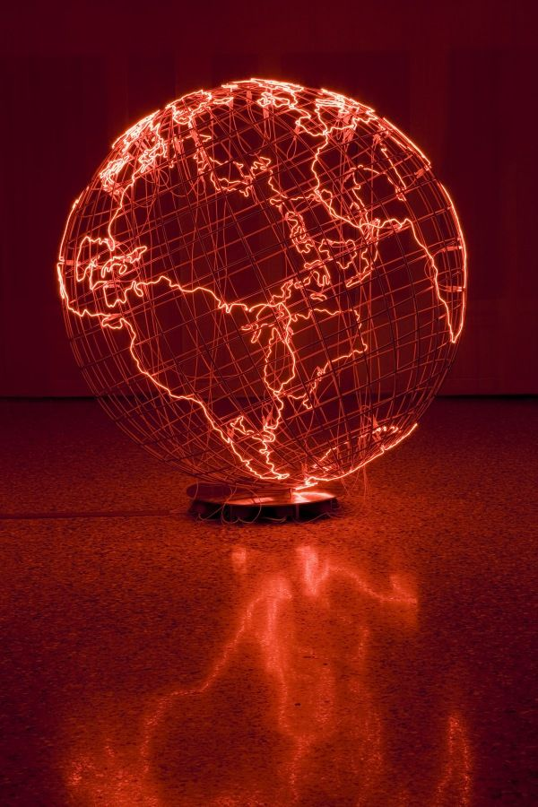 A hollow, wire globe representing the World, with the outlines of landmasses constructed in pink neon