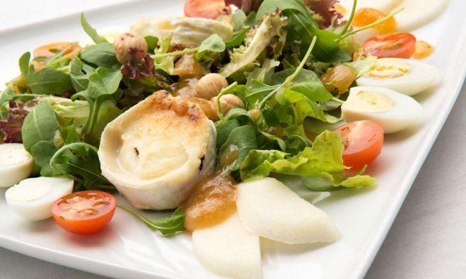 ENSALADA DE QUESO DE CABRA CON VINAGRETA DE MEMBRILLO:  1 rulo de queso de cabra,12 huevos de codorniz,hojas de roble,hojas de lollo  hojas de rúcula,16 tomates cherry,1 pera,50 gr. de membrillo,16 avellanas  harina,agua,aceite de oliva,100 ml. de vinagre de sidra,sal.  Funde el membrillo con el vinagre, cuela, agrega aceite fuera del fuego y una pizca de sal (añade un poco más de vinagre si lo necesita). Reserva la vinagreta de membrillo.