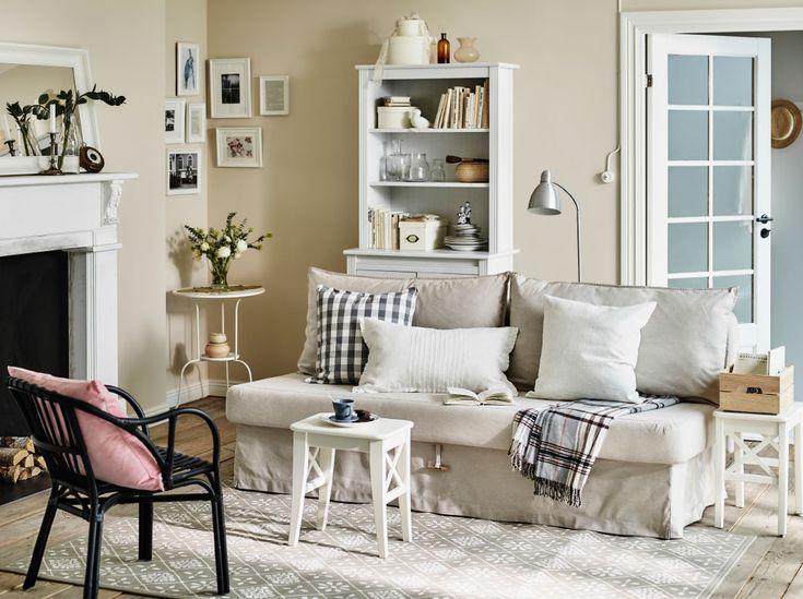 """Ein Wohnzimmer in einem Urlaubshäuschen mit einem HIMMENE 3er-Bettsofa mit Bezug """"Lofallet"""" in Beige und zwei weißen Hockern als Beistelltische"""