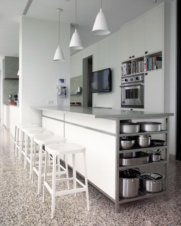 A Family Kitchen Cookbooks and pots and pans are within quick reach on open shelves, and the marble-topped kitchen island is designed to be a gathering place for friends and family. Martha and I often perch there while Alexis tries out new recipes for her blog.