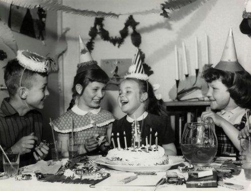 Verjaardagsfeestje met taart met brandende kaarsjes midden op tafel. De kinderen hebben een feestmuts op. Op de achtergrond hangen slingers. Nederland, jaren '50. Voorheen bekend als sfa002008548 en sfa000003980.