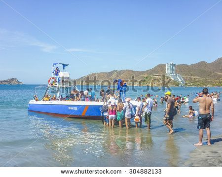 SANTA MARTA, COLOMBIA, JANUARY - 2015 - People aboarding a boat trip to caribbean island from beach at El Rodadero, one of the most famous and visited watering places of Colombia.