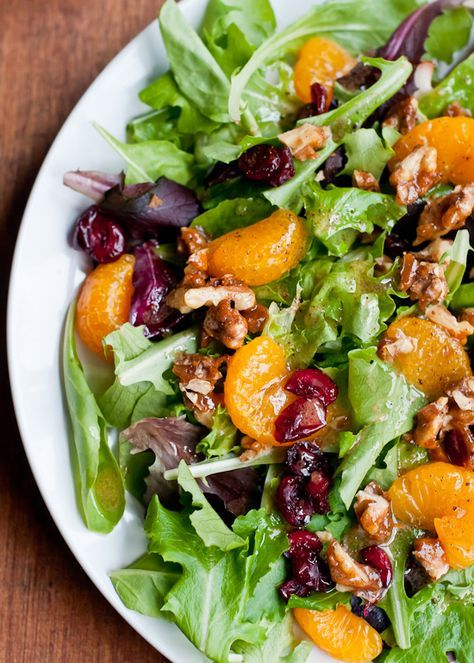 Simple Holiday Green Salad with Orange Vinaigrette - A holiday green salad featuring a mix of baby greens, oranges, dried cranberries and spicy candied walnuts and orange vinaigrette. A vinaigrette consisting of fresh orange juice, white wine vinegar, and a spicy ginger kick. The fresh ginger gives it a burst of freshness, but it's the pinch of cloves and cinnamon that gives it a little something extra that people love. I like to add candied walnuts or pecans for extra crunch and sweetness.