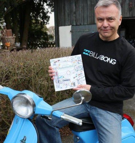Hier sitzt Tom Gehrke in Egweil auf seiner blauen Vespa. In der Hand hält er sein Malbuch.