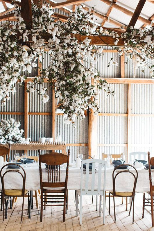 dining table with mismatched chairs in rustic barn with white flowers photographed by luisa brimble. / sfgirlbybay