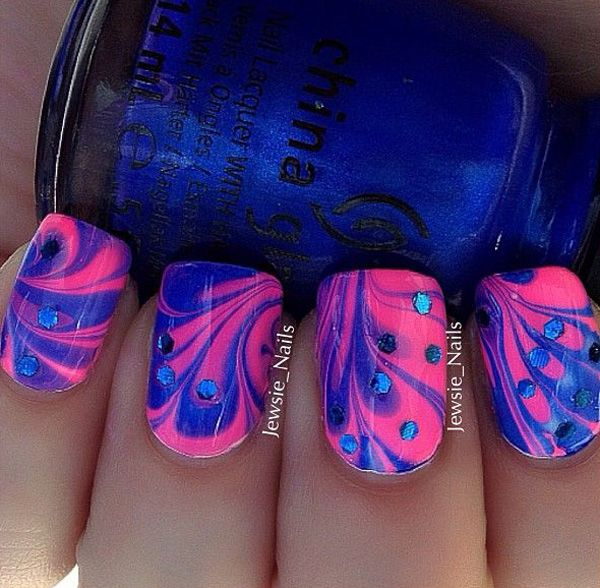 Simply make flower patterns using blue and pink polishes in water marble nail art design and add blue beads on top for effect.