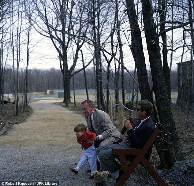 President Kennedy looks on as Under Secretary of the Navy Paul Fay picks up John Jr. while pet dog Charlie looks on at Camp David