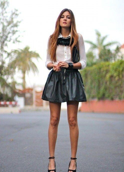 Девушка в короткой расклешенной кожаной юбке, рубашке с черной оборкой и черных босоножках