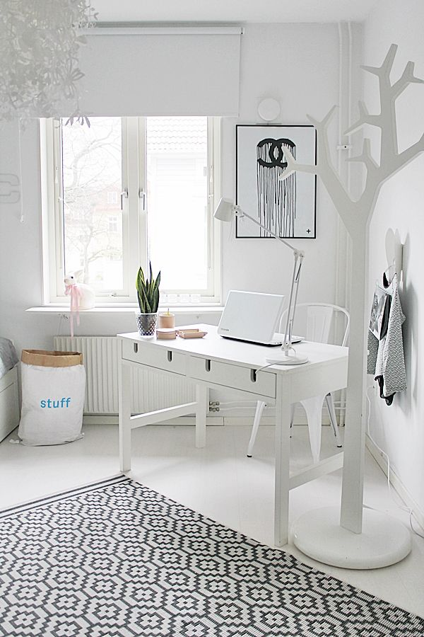 White minimalist Scandinavian bedroom with a distraction-free work space. The clothes hanger tree is nice, imaginative touch.