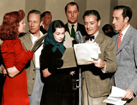 June 11, 1939: the British colony in Hollywood prepare to broadcast their welcome to the King and Queen of Great Britain on their first visit to the United States. From left to right are Greer Garson, Leslie Howard, George Sanders in the rear having a smoke, Vivien Leigh hiding her smoke under her script, Brian Aherne, Ronald Colman, and Basil Rathbone.