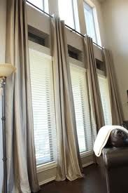 Hate the plain color of these, but shows an idea on how to use curtains properly for large windows.