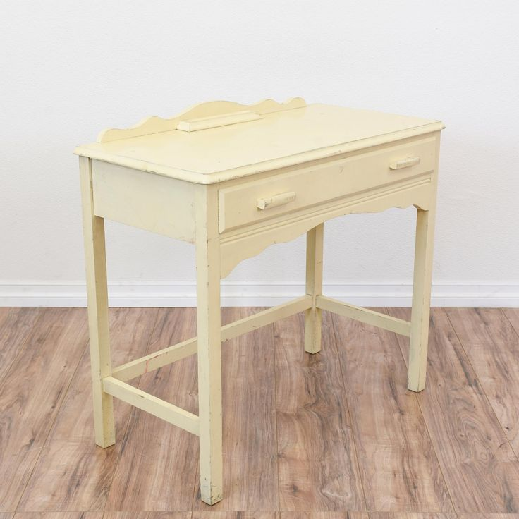 This shabby chic desk vanity is featured in a solid wood with a distressed off white cream paint finish. This desk is in great condition with 1 large drawer, a curved top railing and simple stretcher base. Simple piece perfect for storing a laptop! #shabbychic #desks #kneeholedesk #sandiegovintage #vintagefurniture