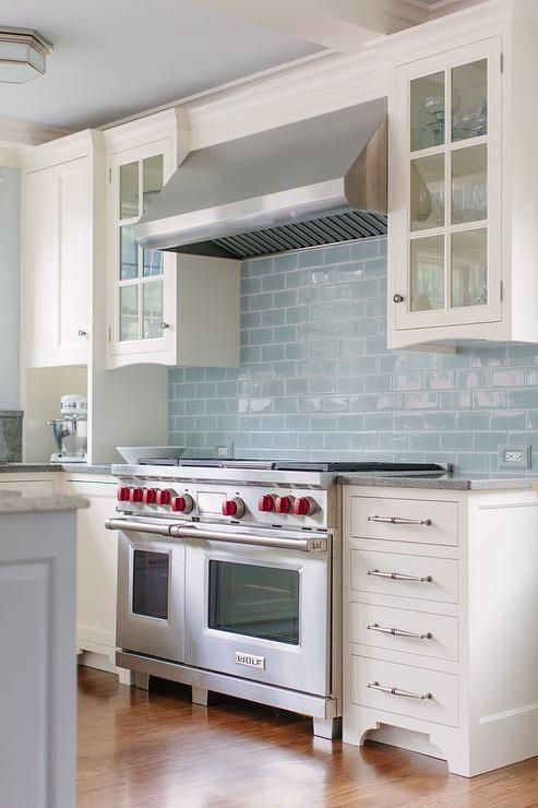 White and blue kitchen features a coffered ceiling with ...