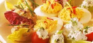 12 hard-boiled British Lion eggs 2 tbsp fat free natural yogurt 1 tsp mild curry powder Salt and pepper 3 tomatoes, sliced 2 spring onions, shredded 1 red chilli, sliced finely coriander, chop Peel & halve the 12 hard-boiled eggs, scoop out yolks and place in a bowl.Mash with a fork and mix 2 tbsp fat free yogurt with the curry powder. Season andspoon the mixture back into the eggs. Push the tops lightly into the coriander and top each with a slice of tomato. Garnish with chilli & spring…