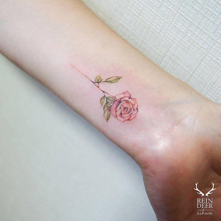 Tatuaje de una rosa de estilo acuarela situado en el interior de la muñeca izquierda.